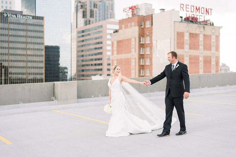 bride and groom pose in wedding attire on rooftop overlooking birmingham alabama skyline