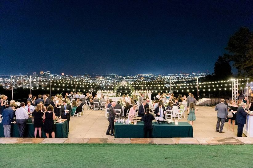 outdoor wedding reception at night overlooking birmingham skyline with string lights and dance floor