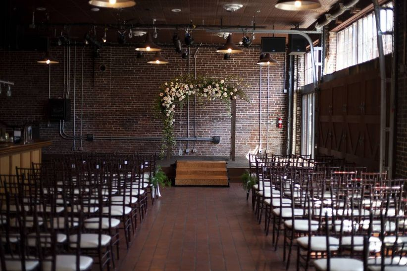 industrial wedding ceremony space with exposed brick and floral arch