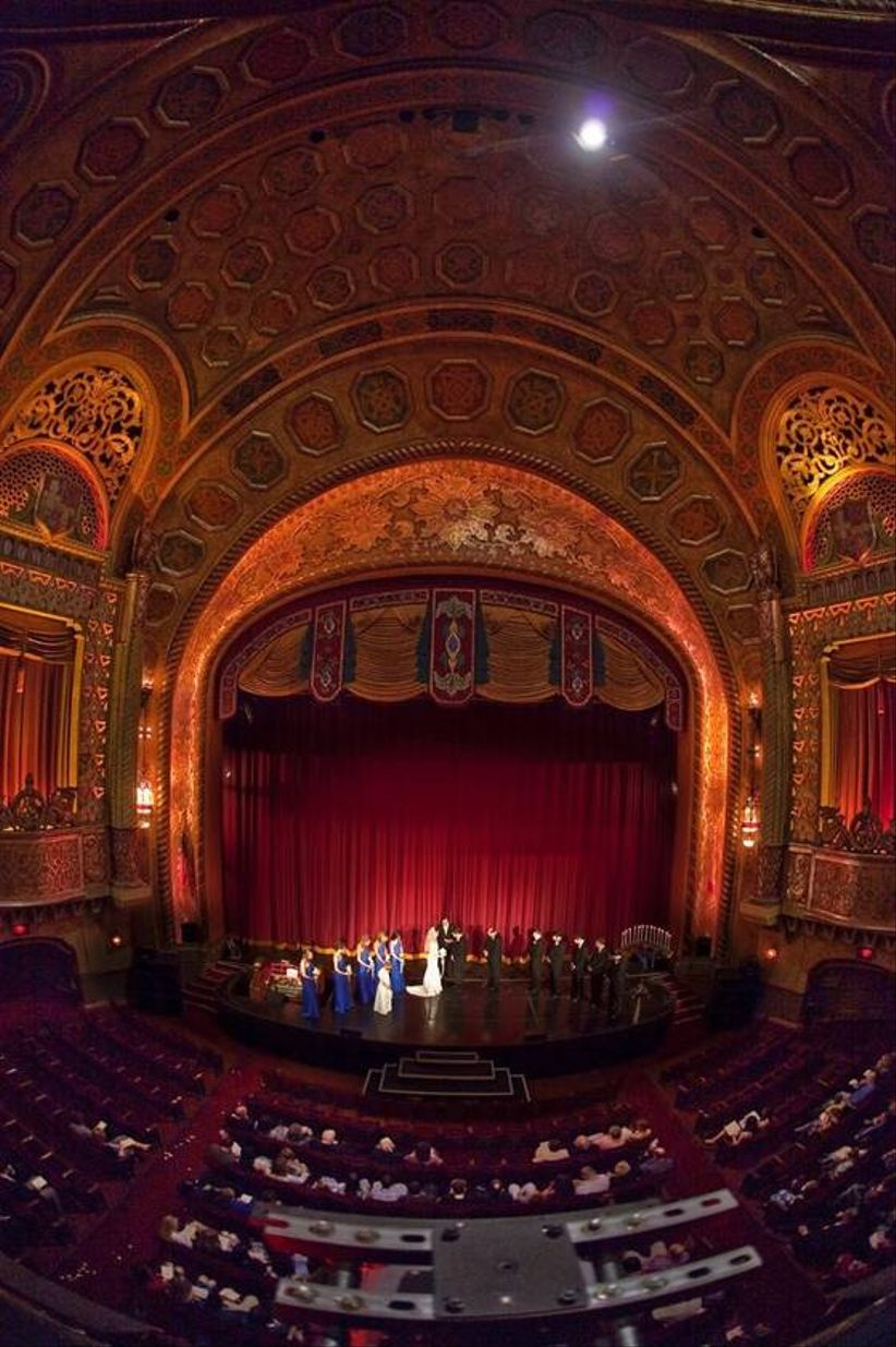 couple standing on theater stage for wedding vows