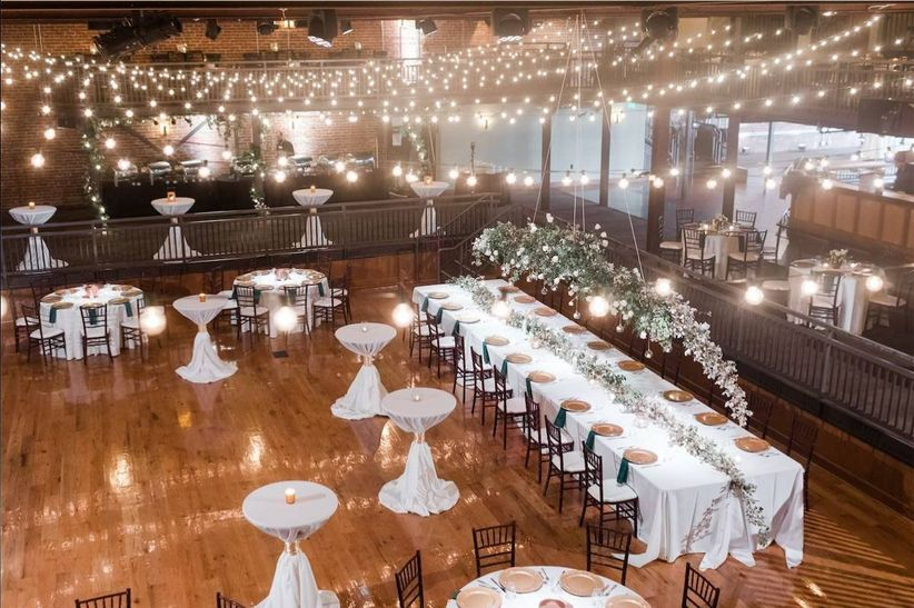 warehouse wedding venue with reception tables and vintage string lights