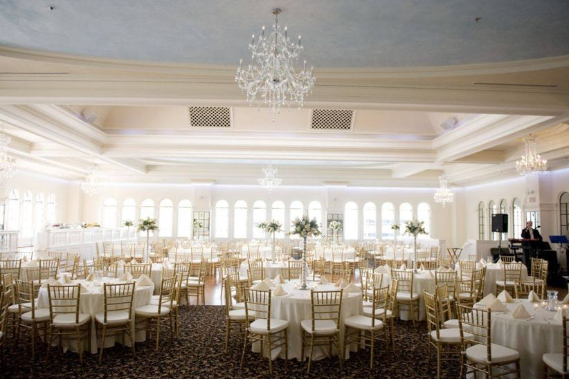 formal ballroom wedding reception with chandeliers and gold chairs