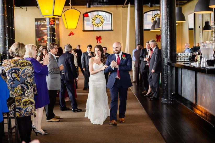 bride and groom walking into wedding reception as guests clap
