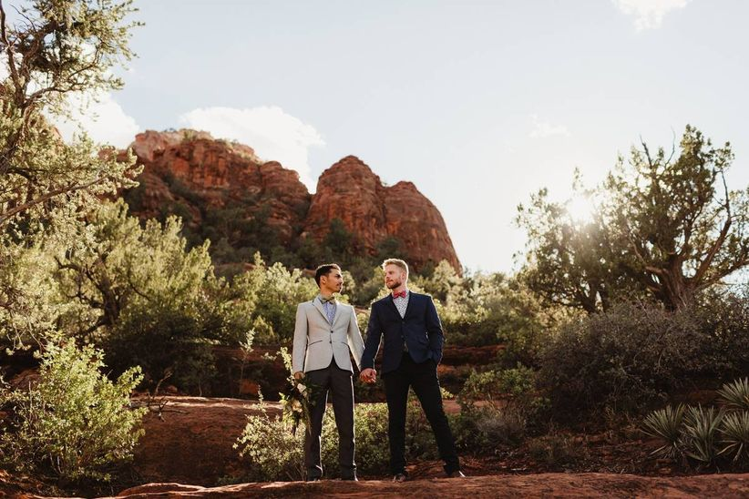 two grooms in suits standing against red rocks desert wedding backdrop