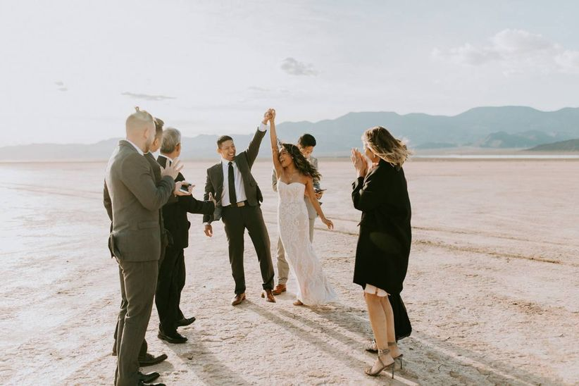 bride and groom surrounded by wedding guests standing in las vegas desert