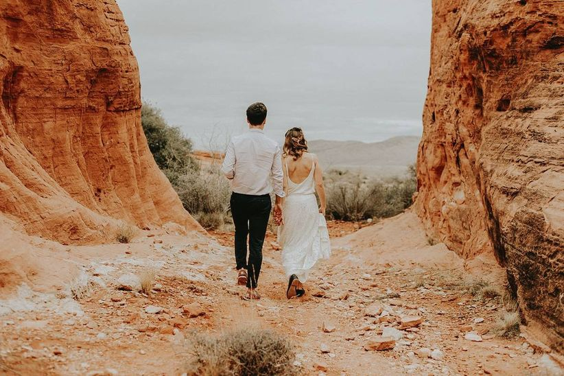 bride and groom wearing casual wedding attire while walking through desert