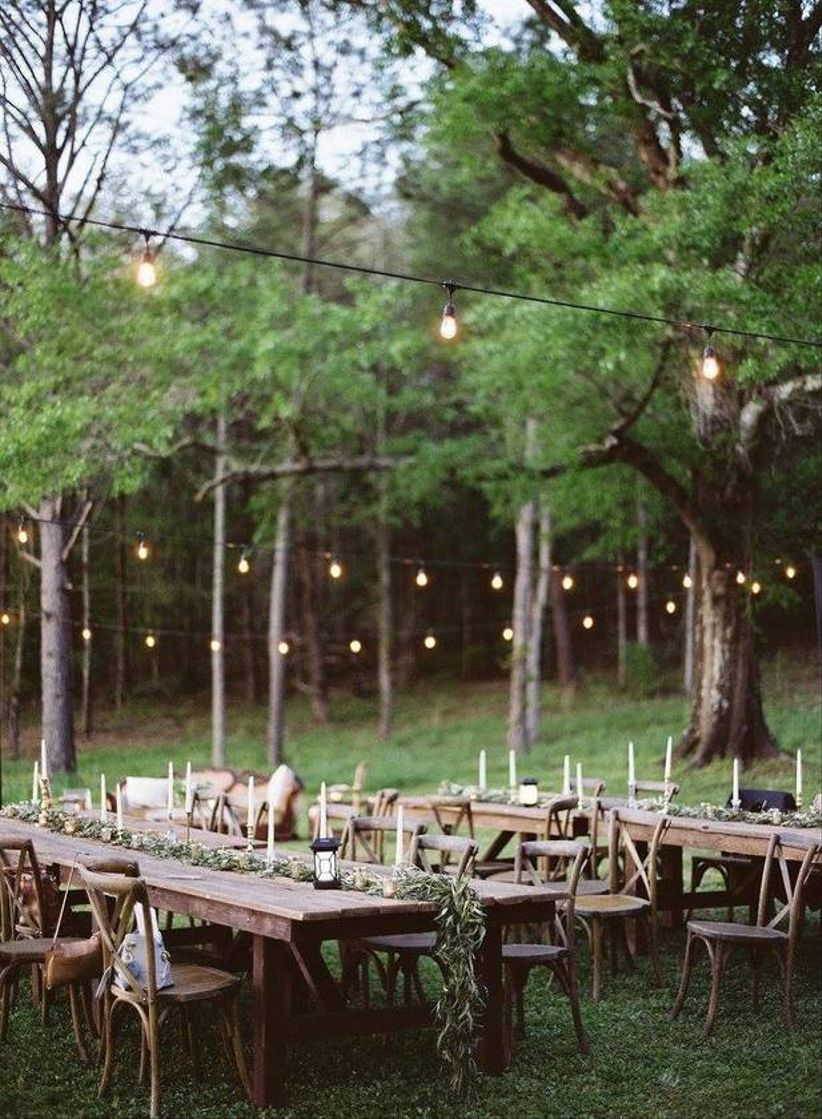 Rustic Outdoor Wedding Reception Tables With Greenery Decor And Strand  Lights