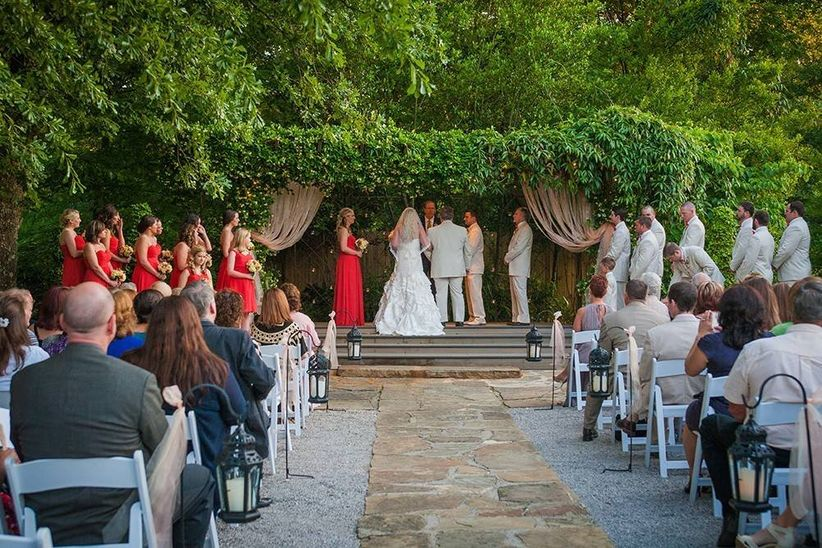 bride and groom stand in ivy covered courtyard for outdoor wedding ceremony