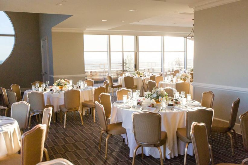 round wedding reception tables with white tablecloths and gold chairs