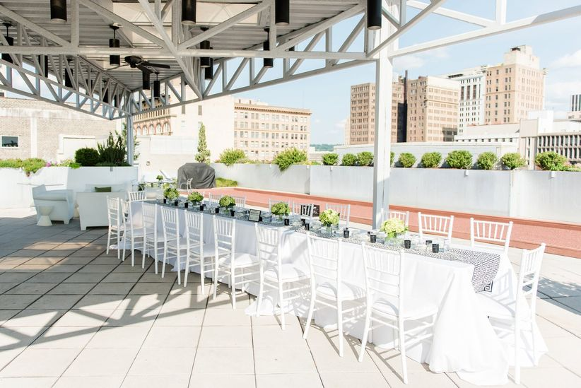 rooftop wedding reception with long guest table and white chairs