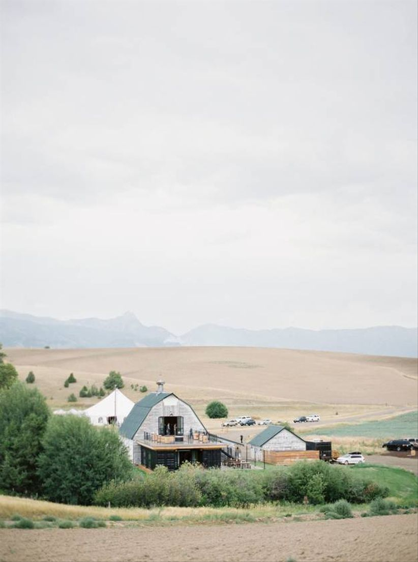 exterior view of a white barn surrounded by trees and mountains