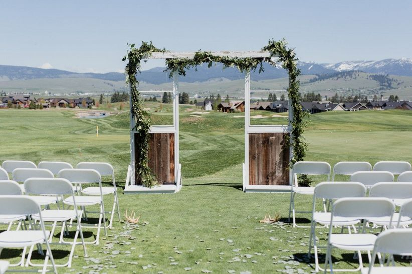 rustic wedding ceremony backdrop made from wood and greenery garlands with mountains in the distance