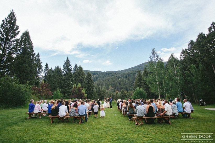 bride and groom exchange vows surrounded by tall pine trees and mountains