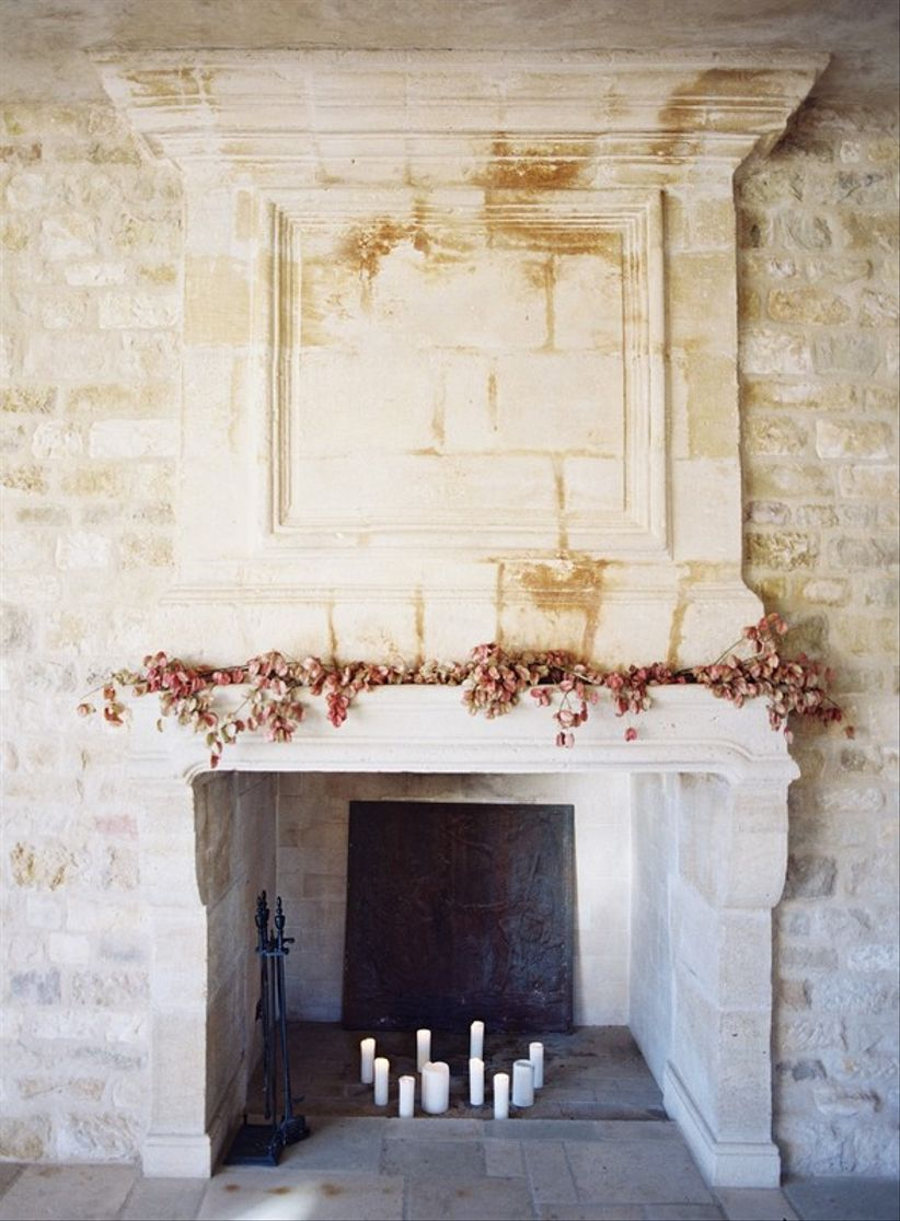stone fireplace decorated with fall foliage and candles