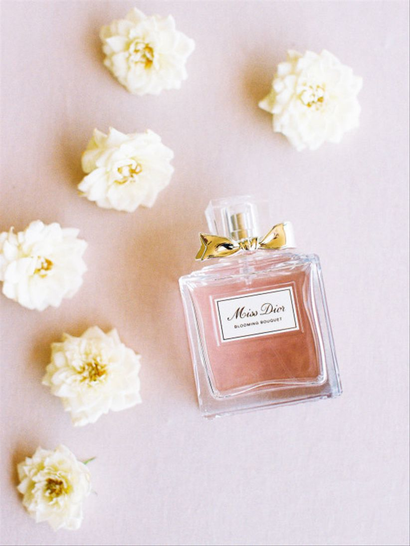miss dior perfume bottle on pink backdrop surrounded by white flowers