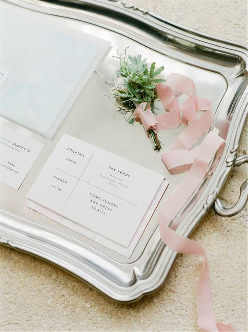 romantic wedding invitations on silver tray with greenery and blush ribbon