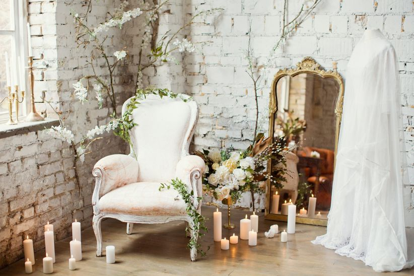 vintage armchair surrounded by white flowers and greenery with candles and wedding dress
