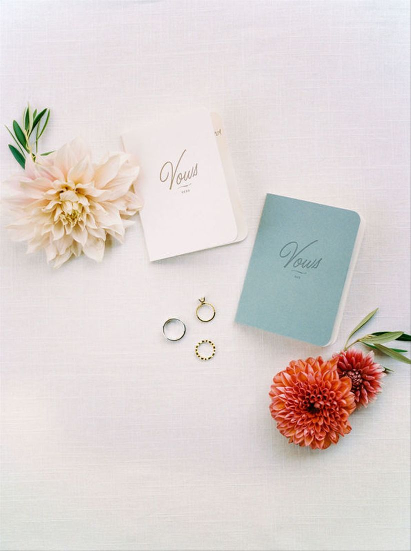 white and teal wedding vow books with wedding rings and fresh flowers