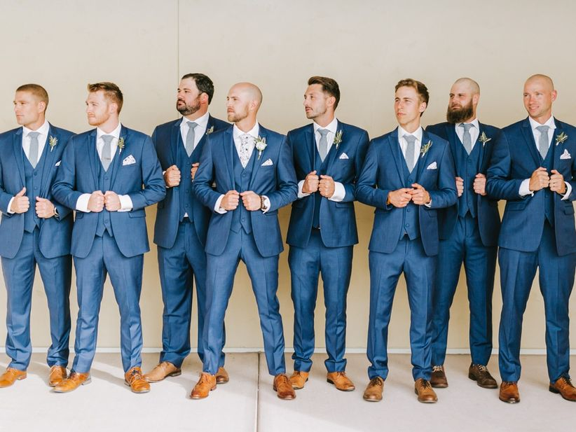 groom and groomsmen wearing blue three-piece suits and brown shoes