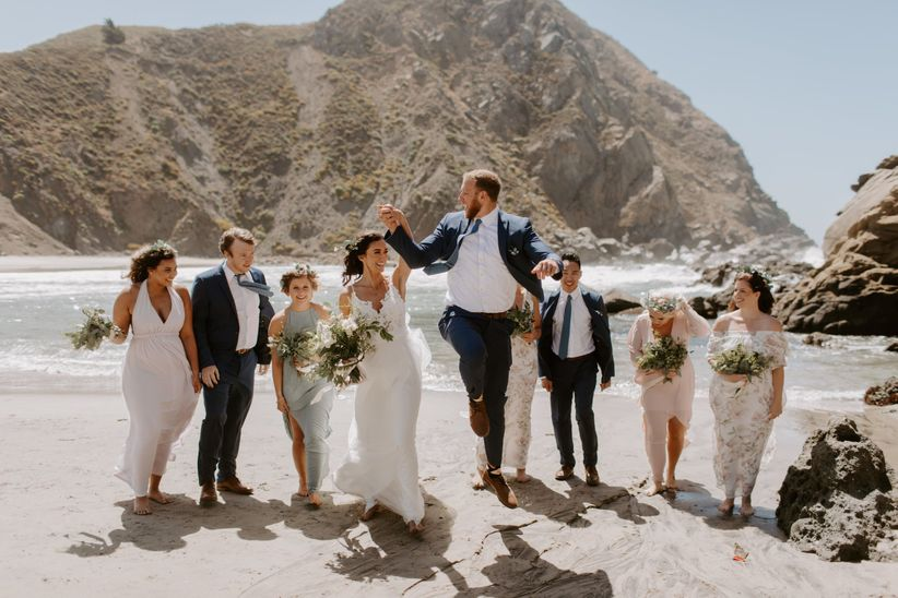 bride and groom with wedding party on beach