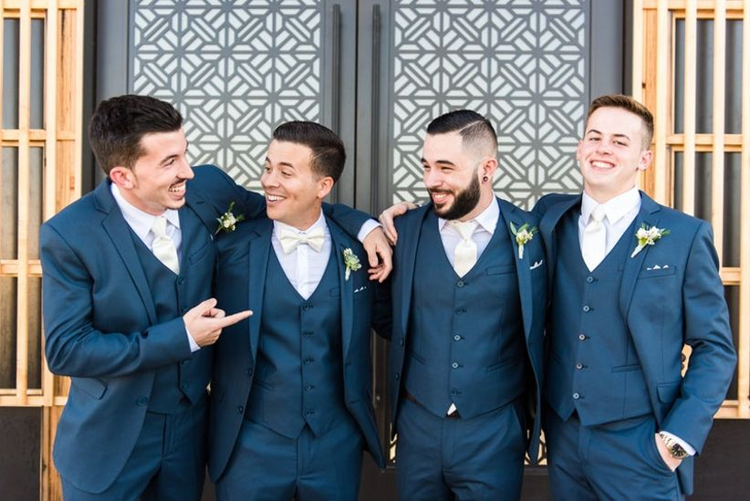 groom with three groomsmen dressed in blue three-piece suits