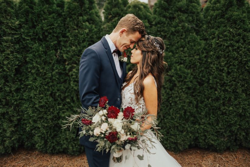 groom wearing navy blue suit poses with bride carrying bouquet