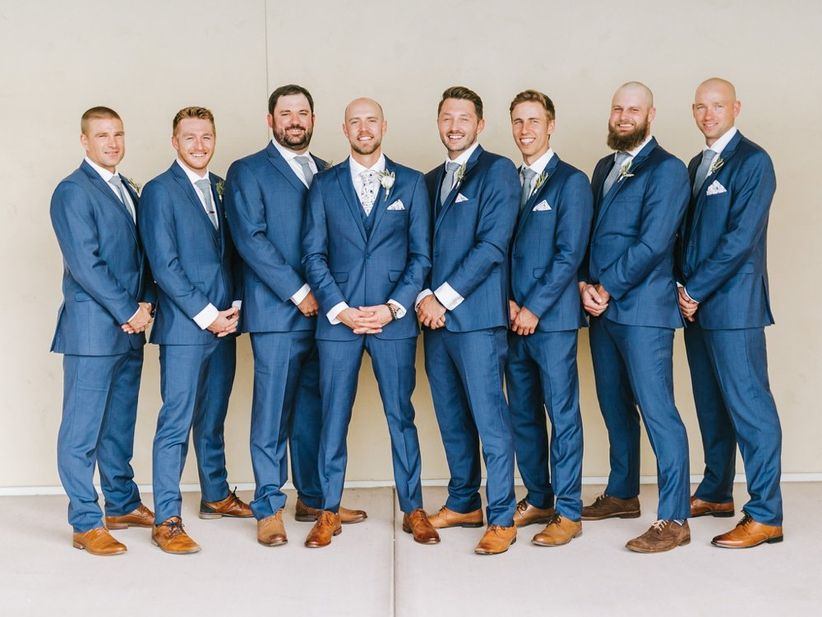 groomsmen wearing blue suits surround the groom