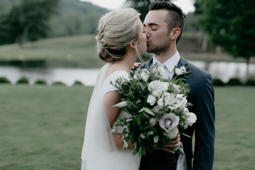 bride holding white wedding bouquet kisses groom wearing blue-green suit