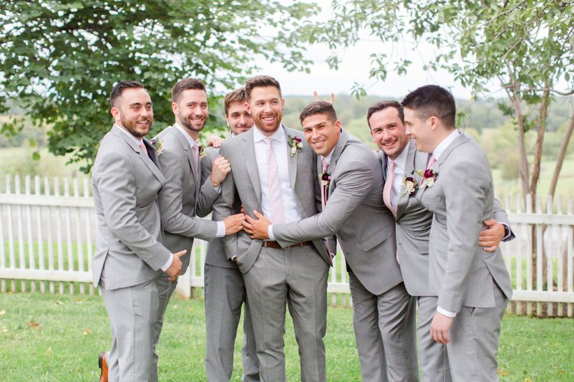 groomsmen in light gray suits with blush pink ties at outdoor wedding venue