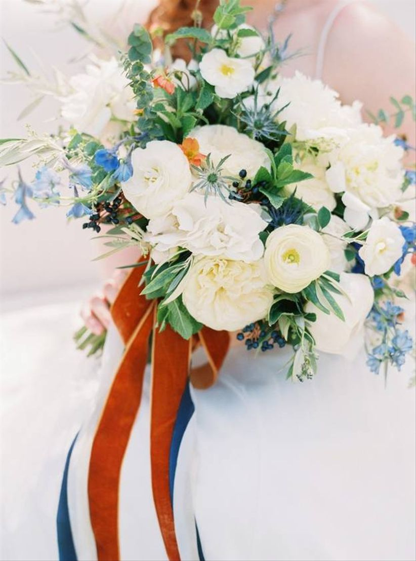 blue and white wedding bouquet with greenery and red ribbons
