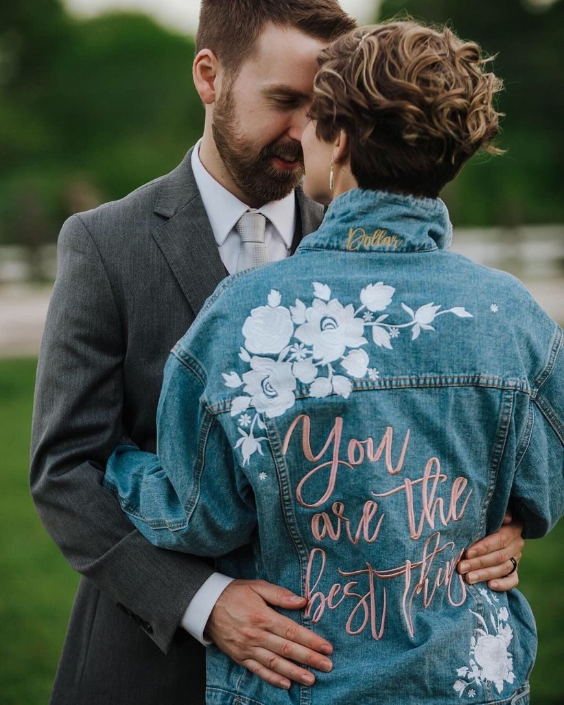bride hugs groom with her back to the camera. she's wearing an oversized denim jacket decorated with white flower patches and