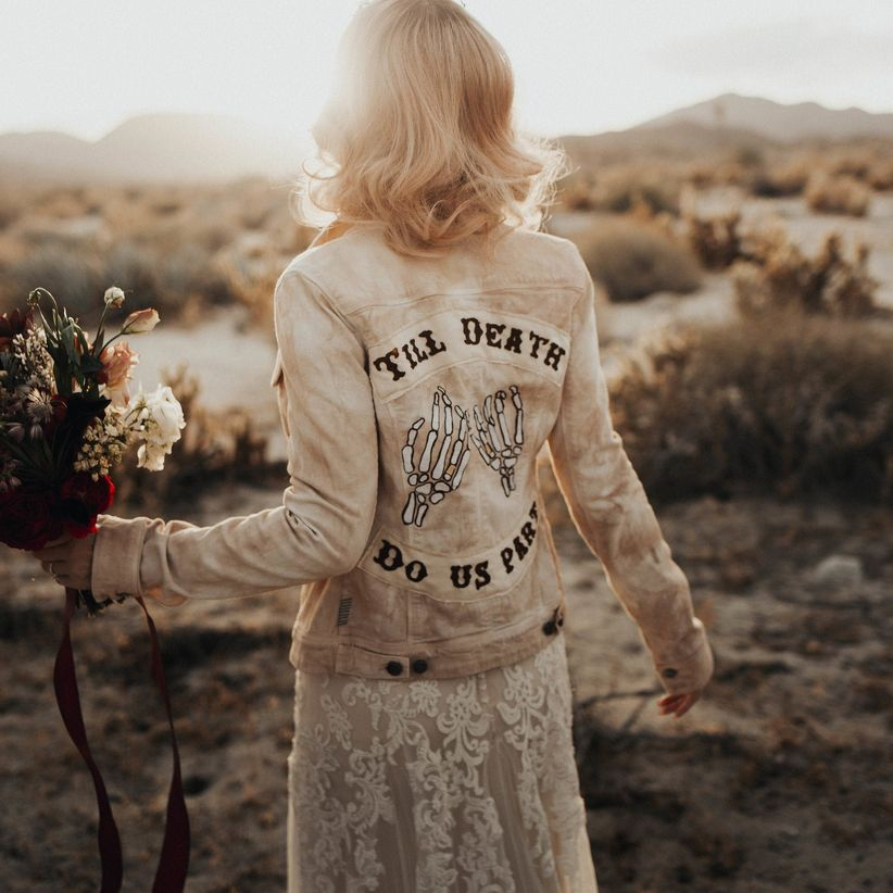 acid-wash denim jacket with skeleton hand patches and