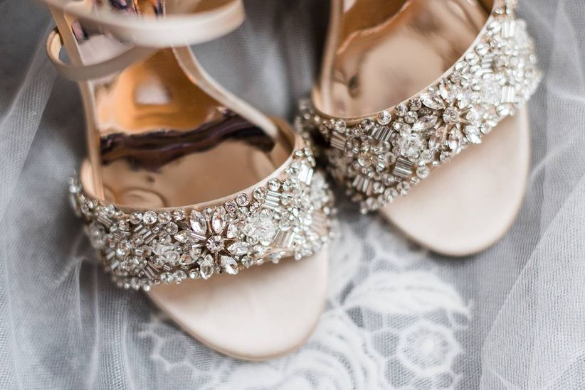 closeup of beaded rose gold wedding sandals on top of tulle veil