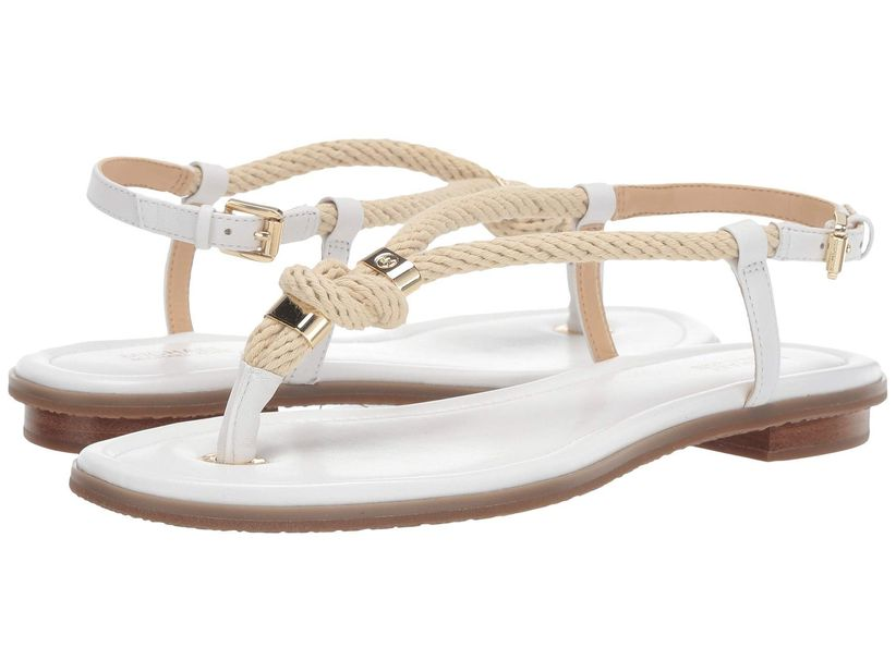 pair of flat white sandals with rope straps and gold buckles