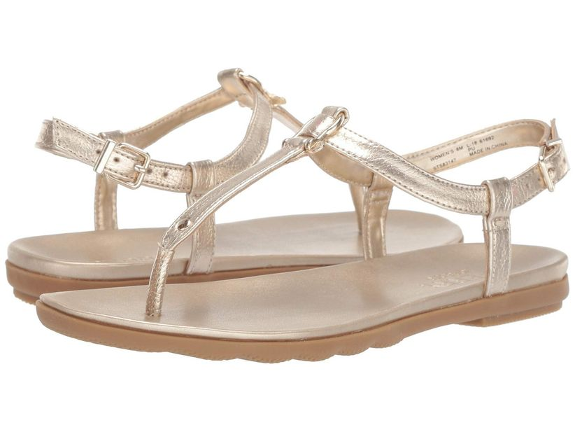 a pair of flat gold thong sandals against a white backdrop