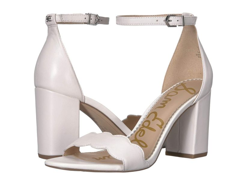 pair of white heeled sandals with scalloped strap at the toe and ankle strap