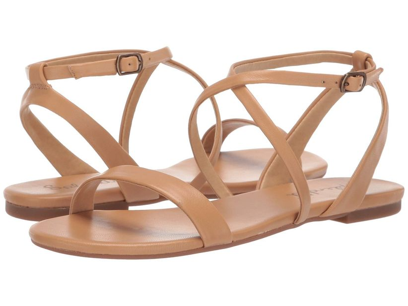 pair of medium skin-tone leather sandals against a white backdrop