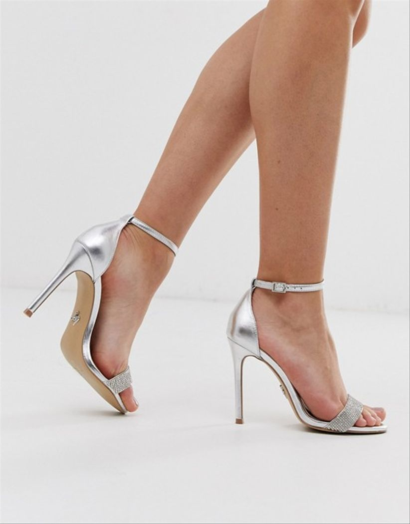 closeup of a model wearing silver ankle strap stilettos against white backdrop