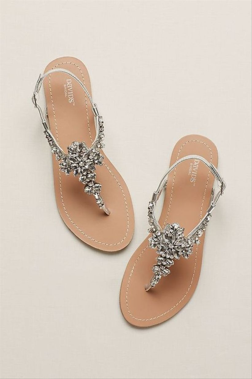 pair of flat thong sandals with beaded silver straps against light gray backdrop