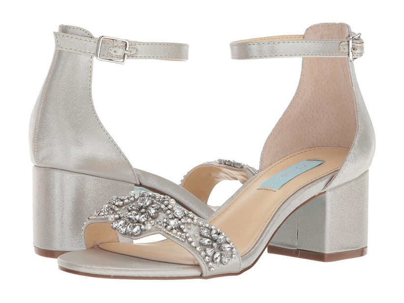 pair of silver low-heel sandals with ankle straps and beaded toe strap