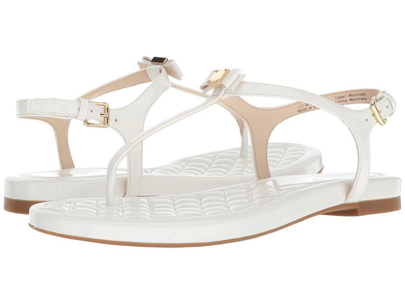 a pair of flat white thong sandals with gold buckles and miniature white bow on the top