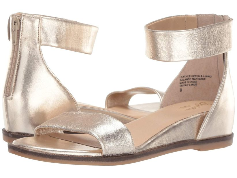 pair of metallic gold ankle strap sandals with hidden wedge heel against a white backdrop