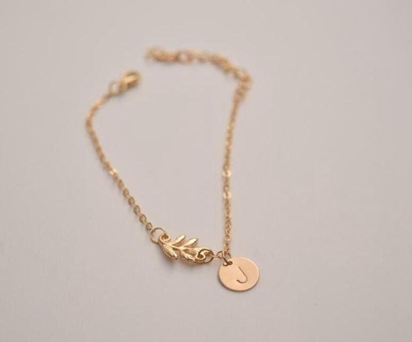 gold chain bracelet with tiny leaf shaped charm and a round charm stamped with the letter
