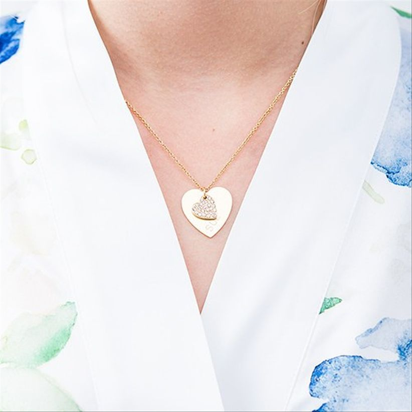 model in floral blue robe wearing a gold heart-shaped necklace with rhinestones