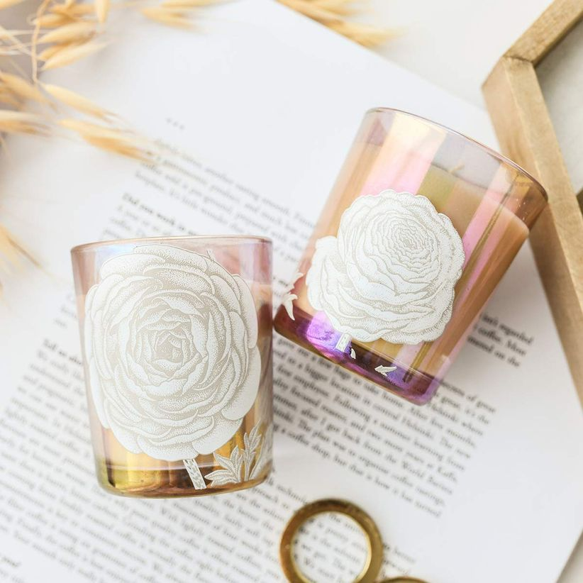 two votive candles in iridescent pink jars decorated with white rose decal