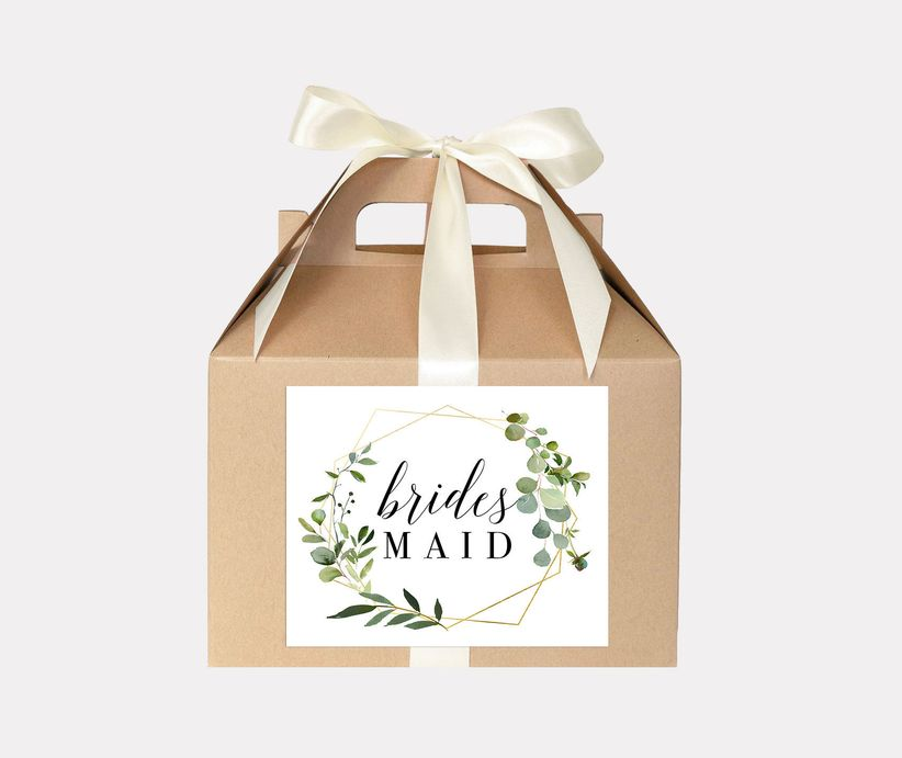 Brown gift box decorated with a white bow and a bridesmaid decal on the front featuring gold geometric and greenery designs
