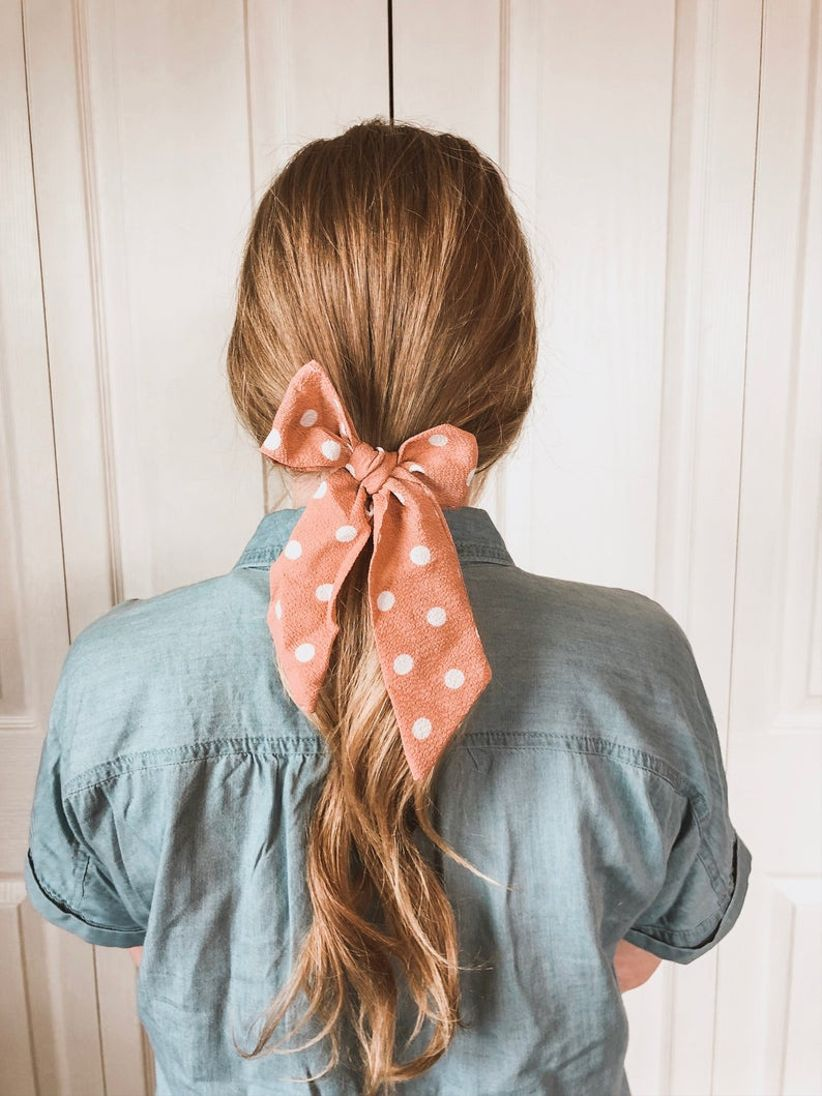 back of model's head wearing a pink polka dot bow with a low ponytail