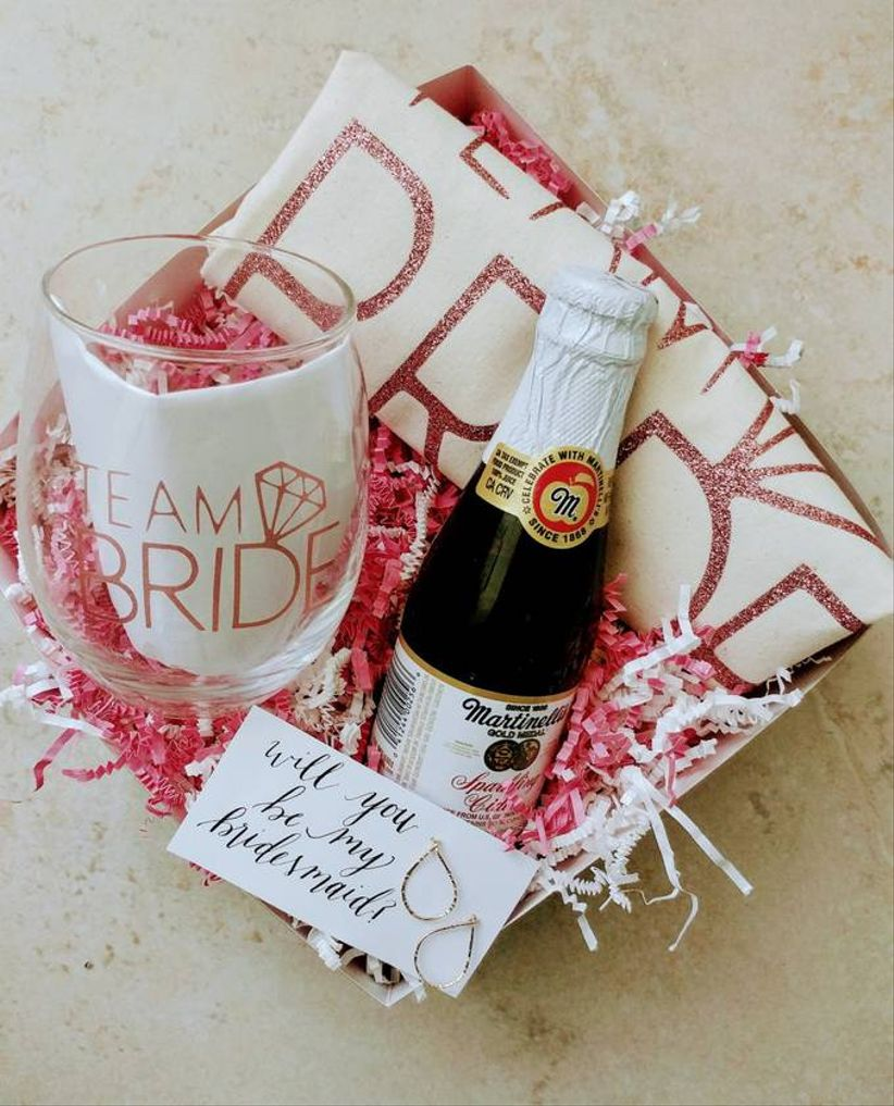 top view of bridesmaid gift box with stemless wine glass, t-shirt, earrings and pink crinkle paper