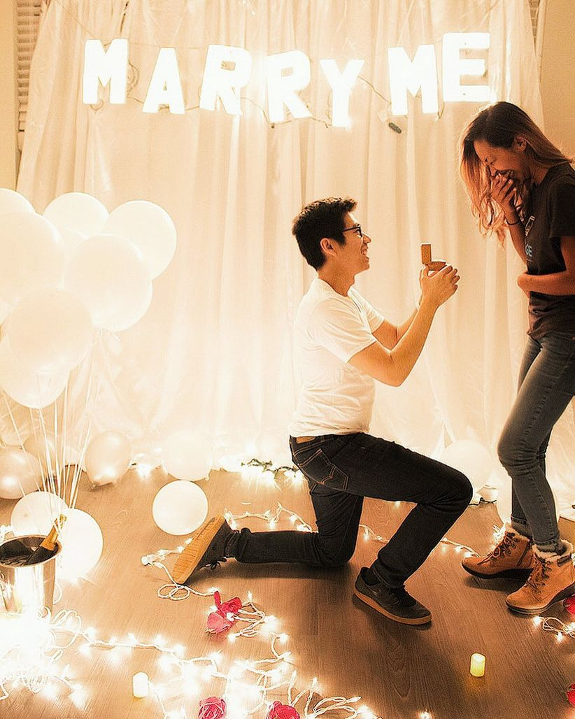 proposal at home with string lights and champagne