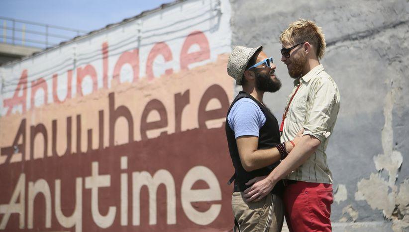 two engaged men hug near a mural in Philadelphia